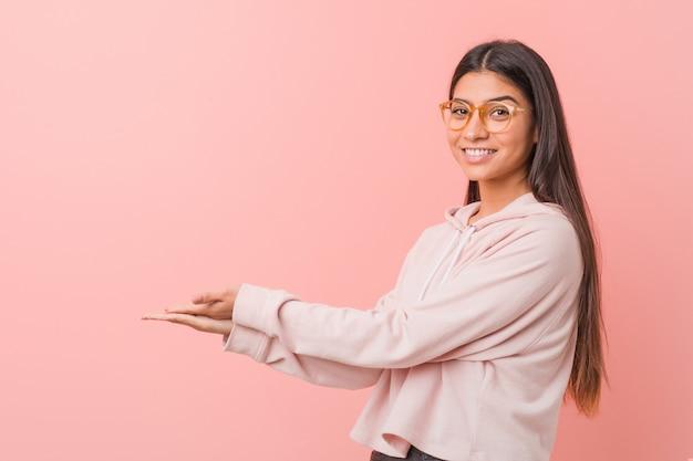 Jeune jolie femme arabe portant un look sport décontracté tenant un espace de copie sur une paume.