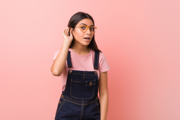 Jeune jolie femme arabe portant une salopette jeans essayant d'écouter un potin.