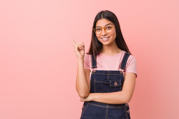 Jeune jolie femme arabe vêtue d'une salopette en jeans souriant gaiement pointant avec l'index.