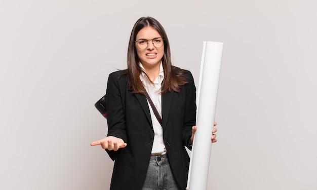 Jeune jolie femme architecte qui a l'air en colère, agacée et frustrée de crier wtf ou qu'est-ce qui ne va pas avec toi