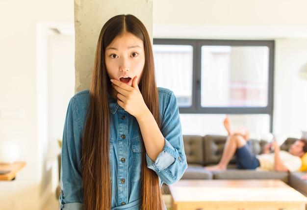 Jeune jolie femme asiatique avec la bouche et les yeux grands ouverts et la main sur le menton