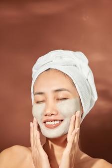 Jeune jolie femme asiatique avec masque cosmétique. spa, concept de beauté.