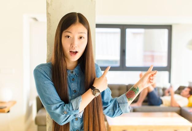 Jeune jolie femme asiatique se sentant choquée et surprise