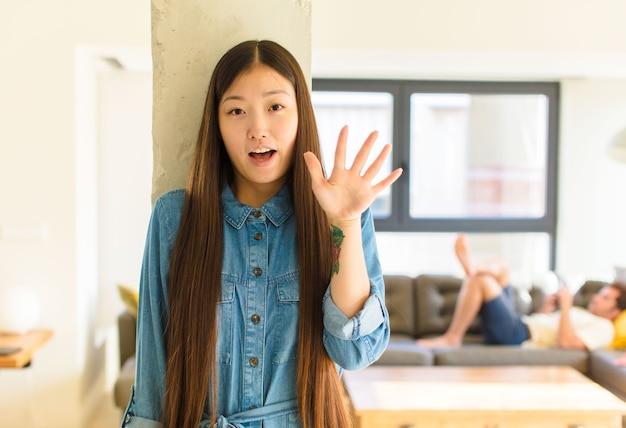 Jeune jolie femme asiatique se sentant stupéfaite et effrayée