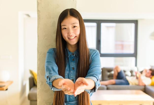 Jeune jolie femme asiatique souriant joyeusement avec un regard amical, confiant et positif