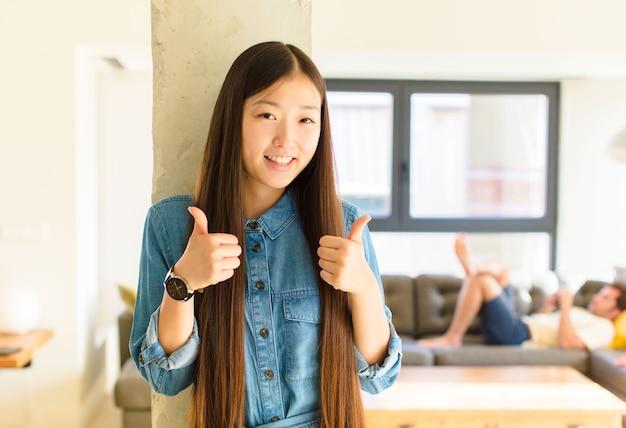 Jeune jolie femme asiatique souriant largement à la recherche heureuse, positive, confiante et réussie, avec les deux pouces vers le haut