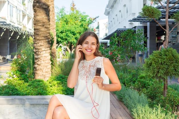 Jeune jolie femme assise sur un banc dans le parc vêtue d'une robe blanche élégante