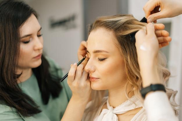 Jeune jolie femme assise sur une chaise et bénéficiant d'un service de maquillage professionnel d'une maquilleuse