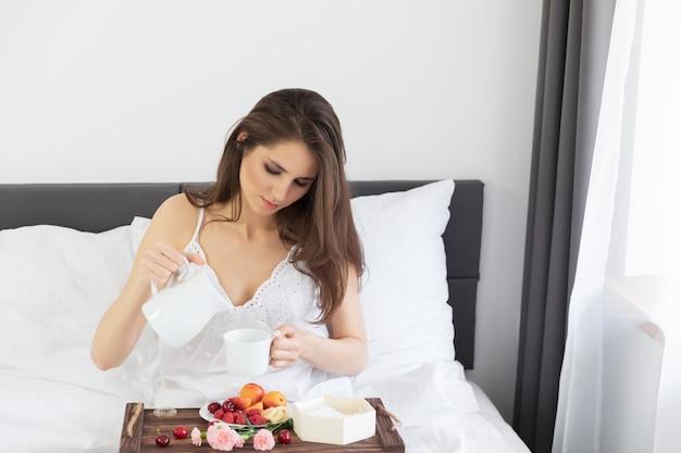 Jeune jolie femme assise dans son lit avec petit déjeuner