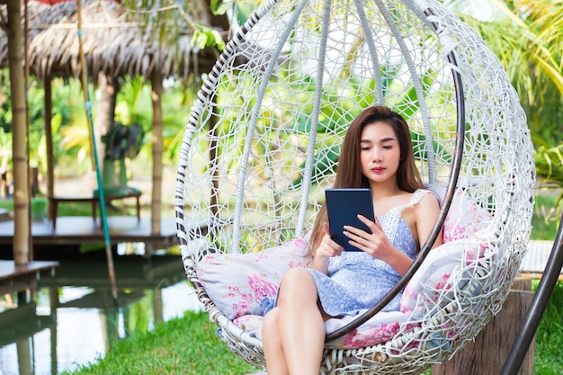 Jeune jolie femme assise utilise un ordinateur portable en balançoire
