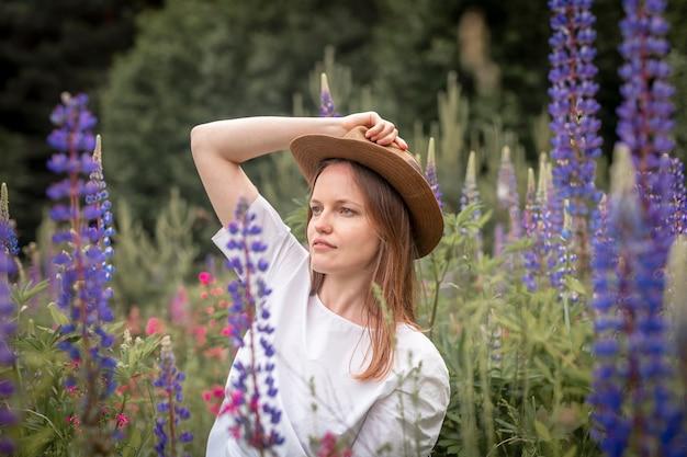 Jeune jolie femme au chapeau assis dans un champ de fleurs de lupin et regardant de côté l'été