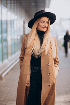 Jeune jolie femme au chapeau noir et manteau beige marchant par mall