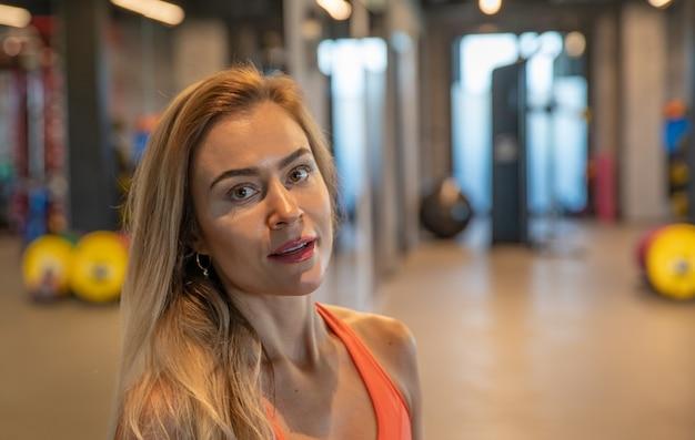 Jeune jolie femme au repos dans la salle de gym après l'exercice