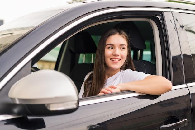 Jeune jolie femme au volant de sa voiture sur route de voyage