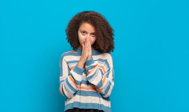 Jeune jolie femme aux cheveux afro et pull rayé posant sur le mur bleu