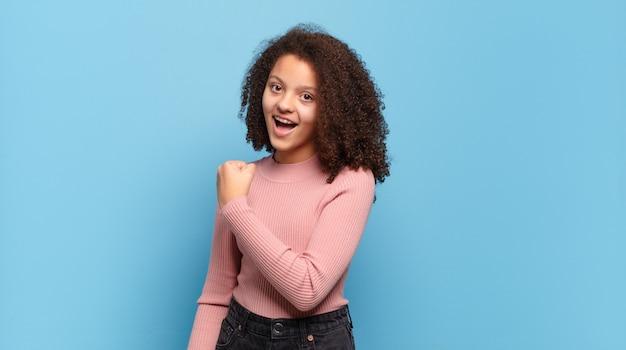 Jeune jolie femme aux cheveux afro et pull rose posant sur le mur bleu