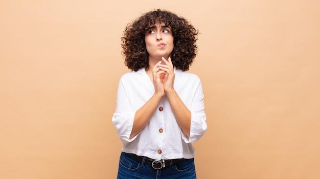Jeune jolie femme aux cheveux bouclés et chemise blanche