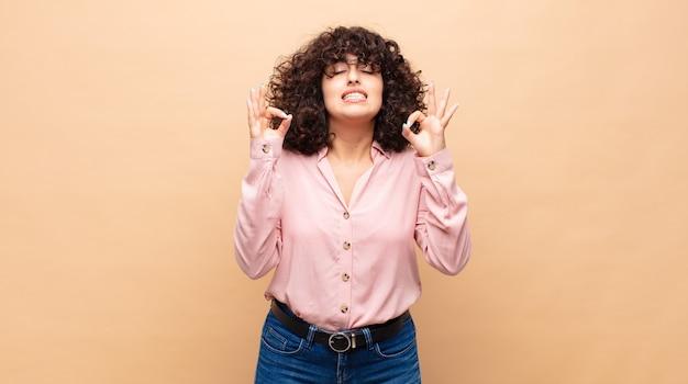 Jeune jolie femme aux cheveux bouclés et une chemise rose