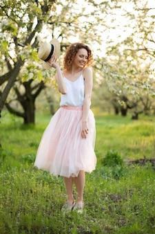 Jeune jolie femme aux cheveux bouclés marchant dans un jardin fleuri vert. humeur romantique de printemps