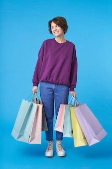 Jeune jolie femme aux cheveux noirs avec une coupe courte avec beaucoup de sacs à provisions