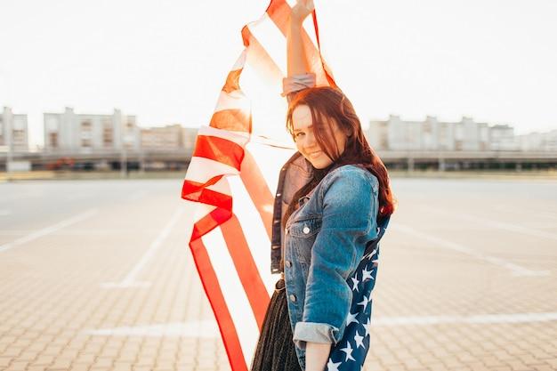Jeune jolie femme aux cheveux rouges enveloppée d'un drapeau national des états-unis sur le soleil.