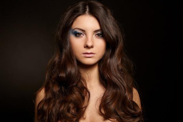 Jeune jolie femme aux longs cheveux noirs maquillage lumineux isolé sur fond noir