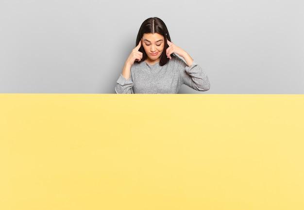 Jeune jolie femme ayant l'air concentrée et réfléchissant à une idée, imaginant une solution à un défi ou à un problème. copiez l'espace pour placer votre concept