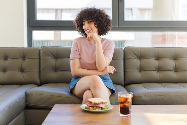 Jeune jolie femme ayant un sandwich assis sur un canapé à la maison