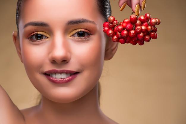 Jeune jolie femme avec des baies dans le concept de beauté
