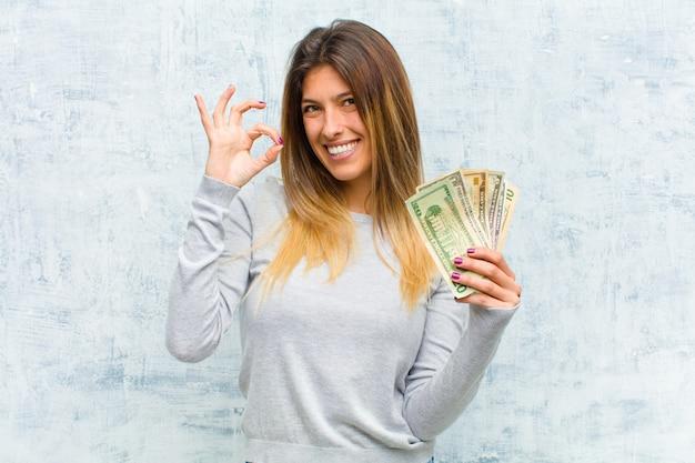 Jeune jolie femme avec des billets contre le mur de grunge