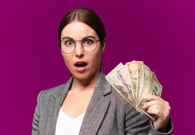 Jeune jolie femme avec des billets en dollars