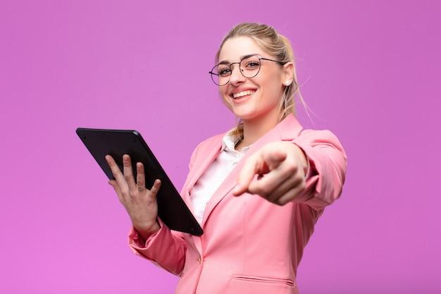 Jeune jolie femme blonde à l'aide d'une tablette