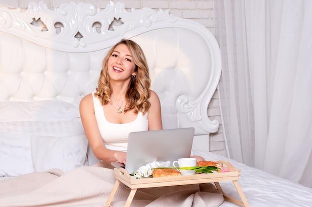 Jeune jolie femme blonde assise sur le lit avec un ordinateur portable prenant son petit déjeuner, un pigiste ou un blogueur à la maison.