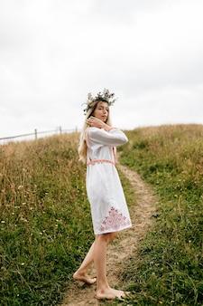 Jeune jolie femme blonde aux pieds nus robe blanche