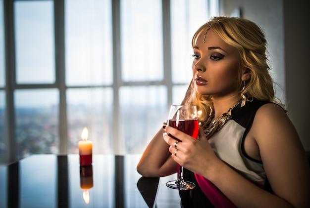Jeune jolie femme blonde en bijoux est assise à une table avec une bougie allumée et boit du jus