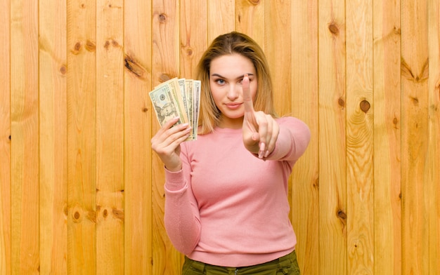 Jeune jolie femme blonde avec des billets de dollar contre le mur en bois