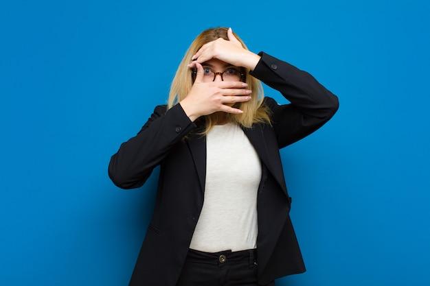 Jeune jolie femme blonde couvrant le visage avec les deux mains disant non à la caméra! refuser des photos ou interdire des photos contre un mur plat