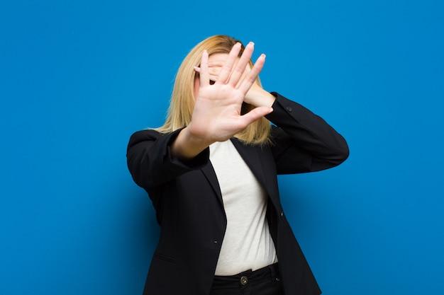 Jeune jolie femme blonde couvrant le visage avec la main et mettant l'autre main à l'avant pour arrêter l'appareil photo, refusant les photos ou les images contre un mur plat