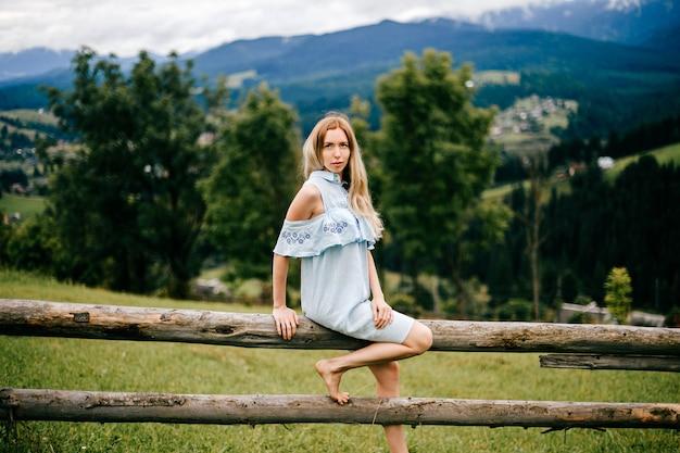 Jeune jolie femme blonde élégante robe romantique bleue