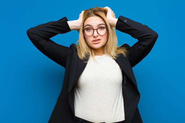 Jeune jolie femme blonde frustrée et agacée, malade et fatiguée de l'échec, marre des tâches ennuyeuses et ennuyeuses sur un mur plat