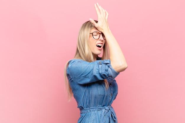 Jeune jolie femme blonde levant la paume au front pensant oups, après avoir fait une erreur stupide ou s'être souvenue, se sentir stupide