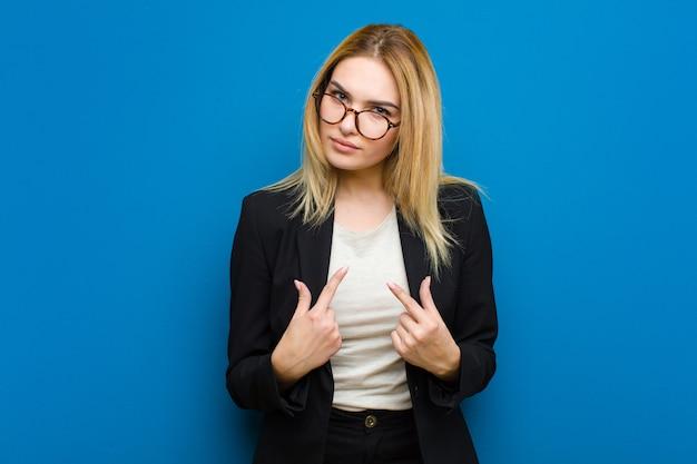 Jeune jolie femme blonde pointant sur elle-même avec un regard confus et interrogateur, choquée et surprise d'être choisie sur un mur plat
