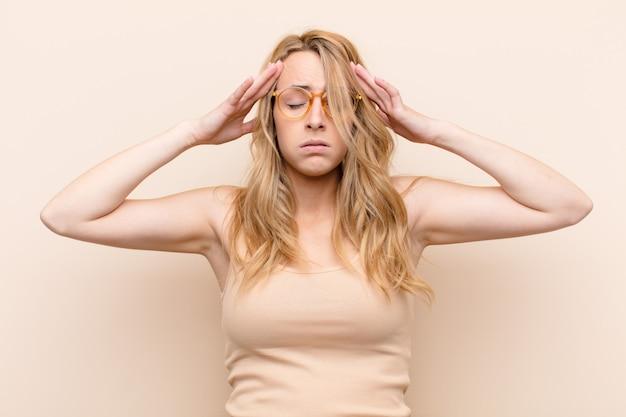 Jeune jolie femme blonde à la recherche concentrée, réfléchie et inspirée, remue-méninges et imaginer avec les mains sur le front sur le mur de couleur