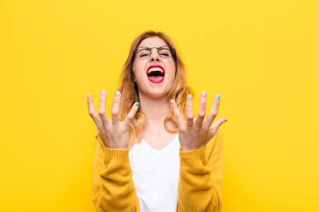Jeune jolie femme blonde à la recherche désespérée et frustrée, stressée, malheureuse et ennuyée, criant et criant contre le mur jaune