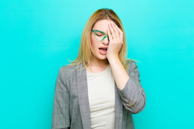 Jeune jolie femme blonde à la recherche de sommeil, s'ennuie et bâille, avec un mal de tête et une main couvrant la moitié du visage contre un mur plat