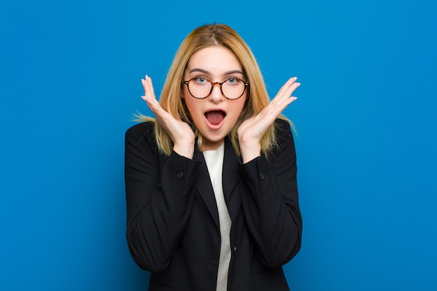 Jeune jolie femme blonde se sentant choquée et excitée, en train de rire, émerveillée et heureuse à cause d'une surprise inattendue contre un mur plat