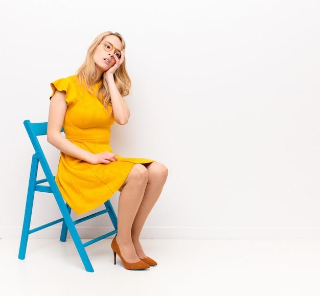 Jeune jolie femme blonde se sentant ennuyée, frustrée et endormie après une tâche fastidieuse, ennuyeuse et fastidieuse, tenant le visage avec la main contre le mur de couleur plat