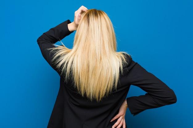 Jeune jolie femme blonde se sentant perplexe et confuse, pas sûre de la bonne réponse, essayant de faire un mur plat de choix