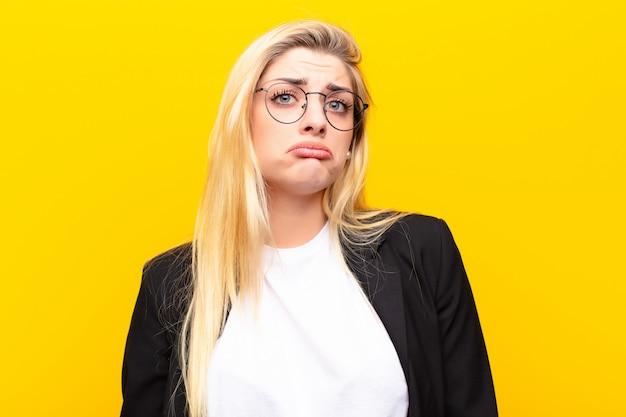 Jeune jolie femme blonde se sentant triste et pleurnichard avec un regard malheureux contre le mur jaune