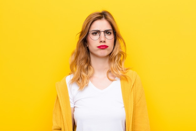 Jeune jolie femme blonde se sentant triste et pleurnichard avec un regard malheureux, pleurant avec une attitude négative et frustrée contre le mur jaune